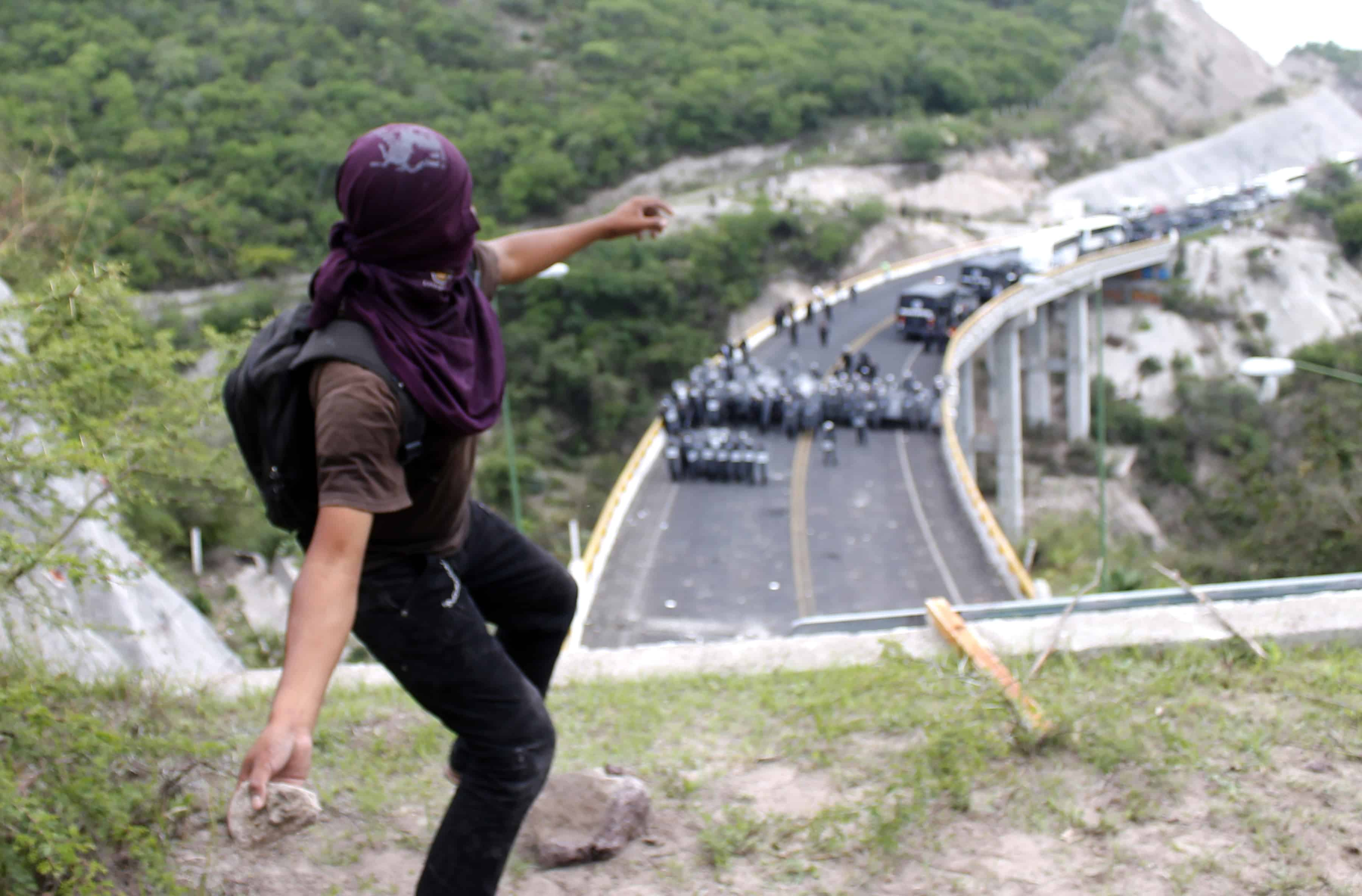 A protester from Ayotzinapa throws stones at the Mexican Federal Police blocking the Chilpancingo-Tixtla highway.