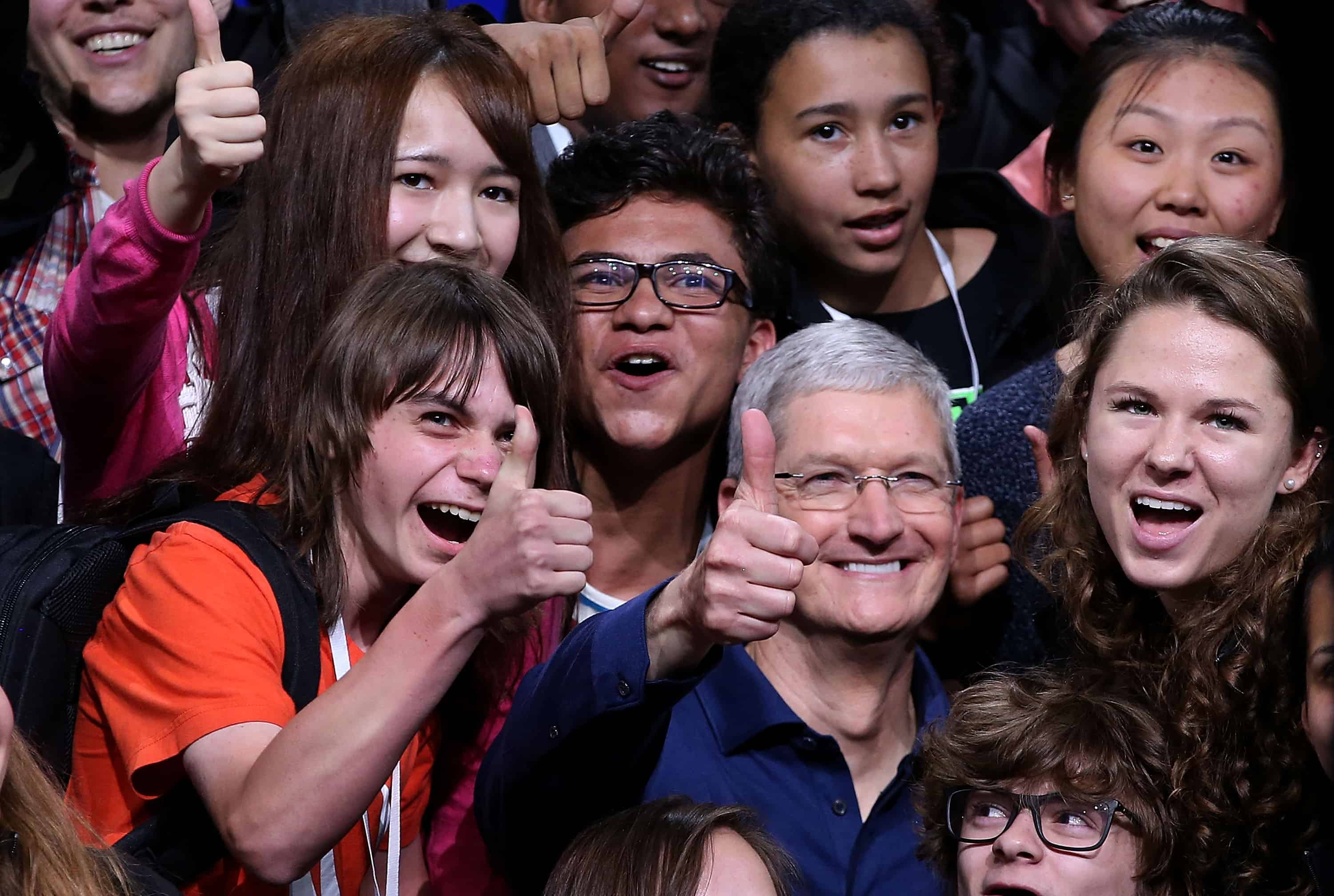 Apple CEO Tim Cook, center, poses for a photo with high school kids.