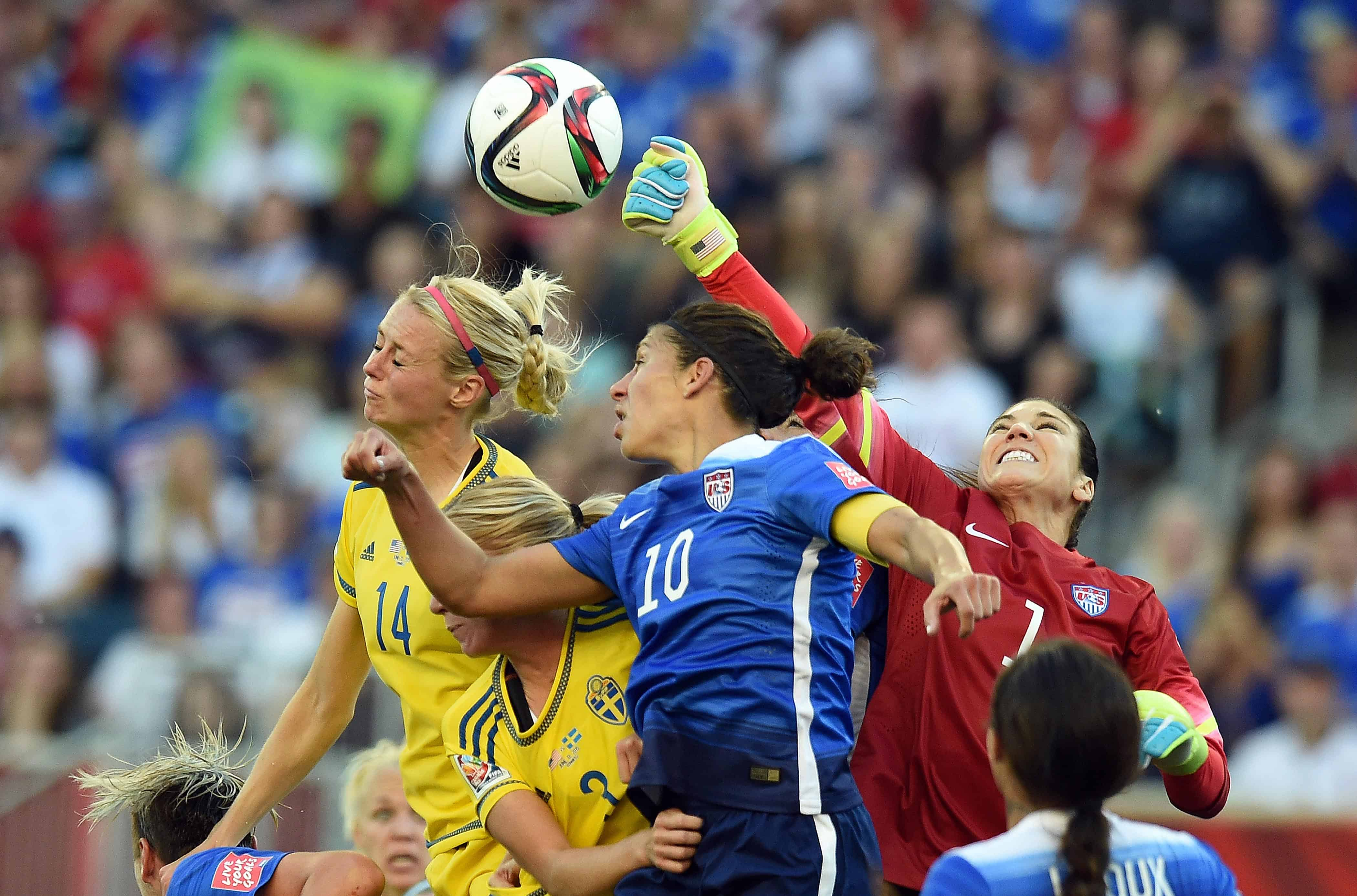 U.S. goalkeeper Hope Solo, right, punches the ball away.
