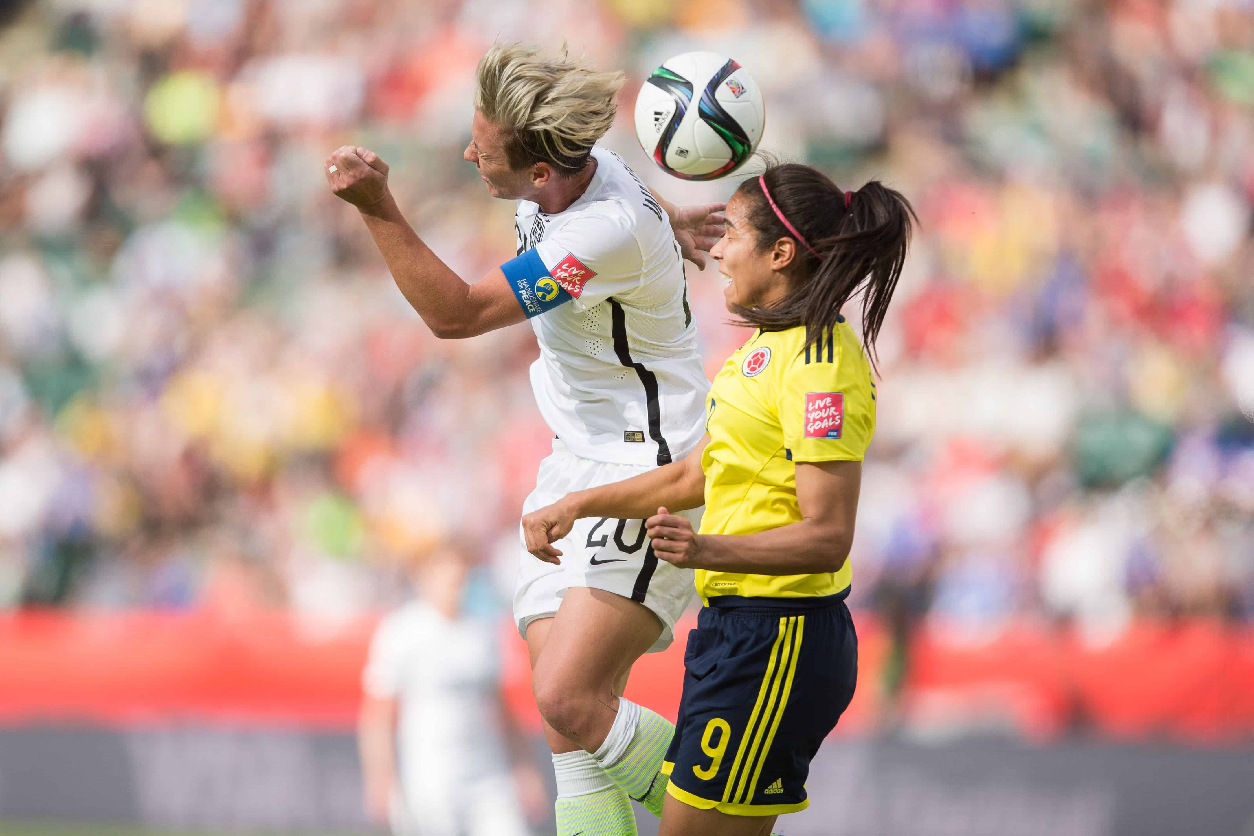 USA's Abby Wambach, left, and Colombia's Orianica Velasquez jump for the ball.