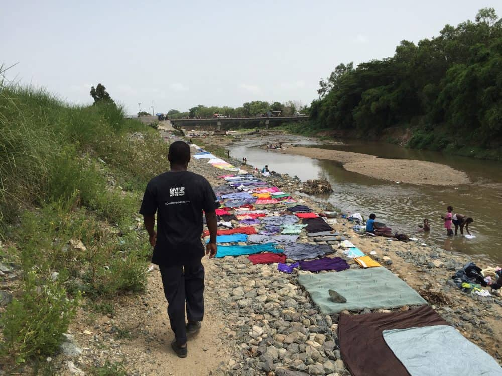 Smith Laflur walks along the banks of the Massacre River through Ouanaminthe, Haiti.