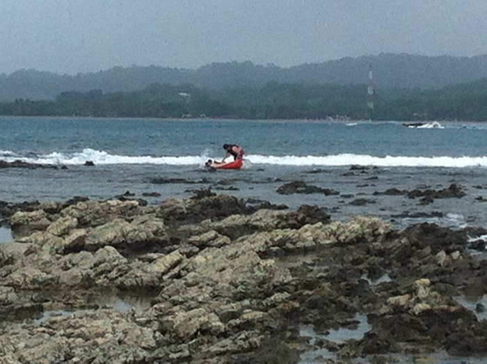 Shipwreck! Two men struggle with a kayak that overturned on the rocks of Isla Chora.