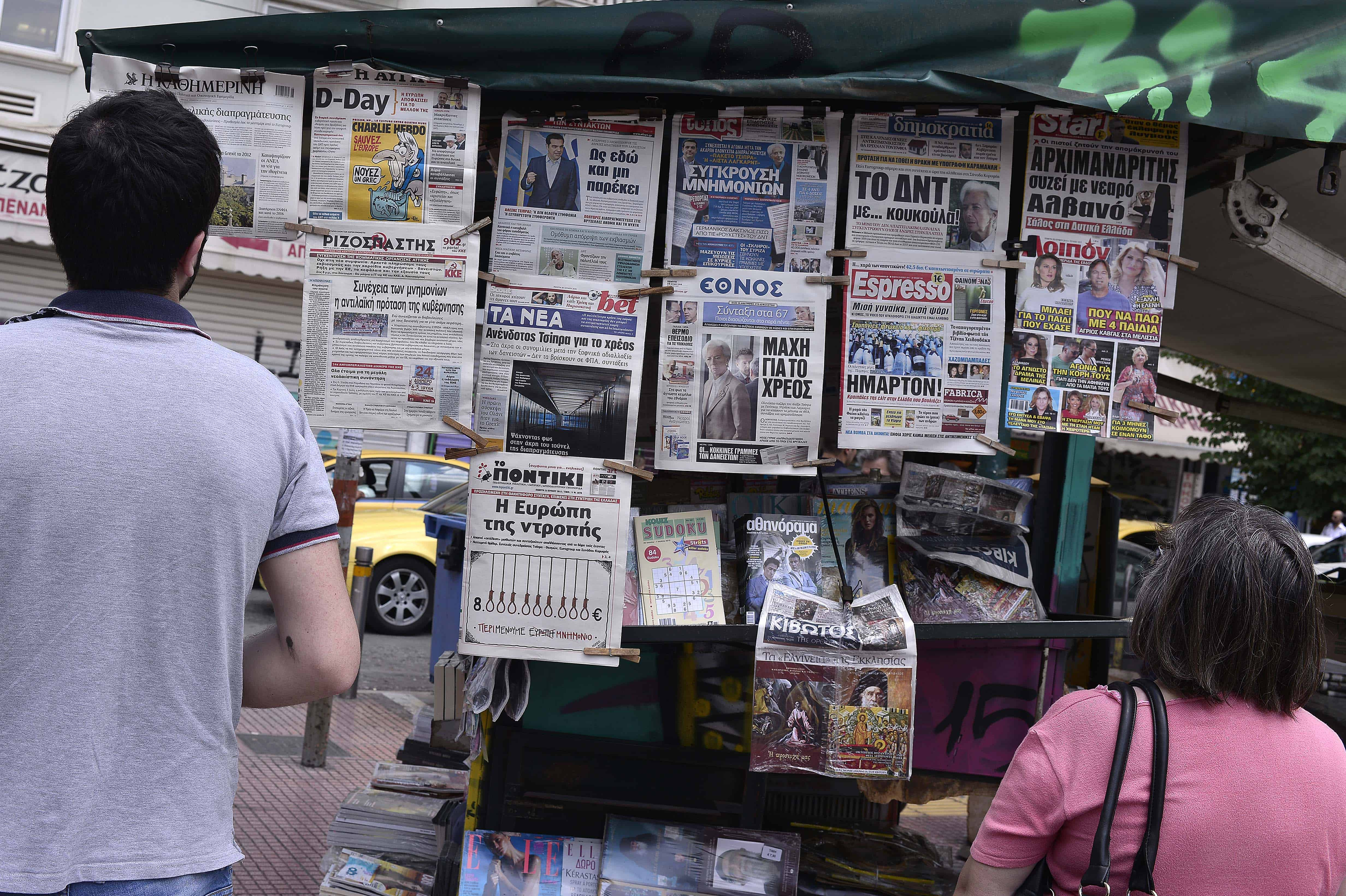 Onlookers view newspaper headlines in central Athens on June 25, 2015.