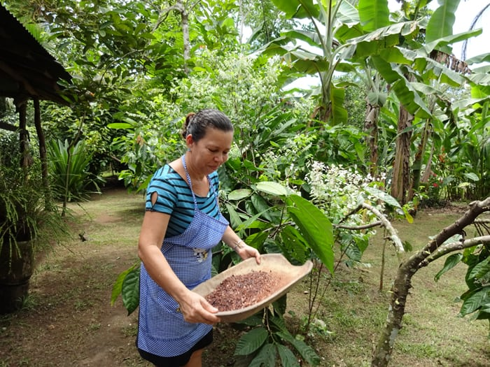 Rosy Quirós shakes crushed cacao beans into the air to make the shells blow away.