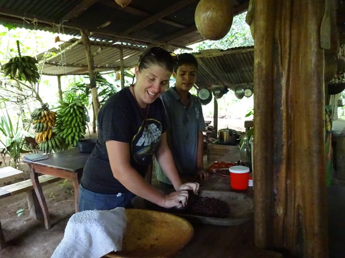 Shana Stratton of Smartsville, California, uses a stone to grind roasted cacao beans in order to remove the shells.