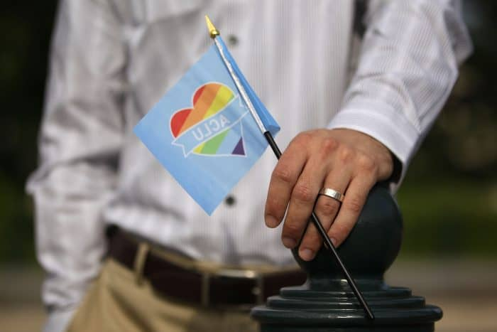 A man holds a rainbow flag in support of same-sex marriage.