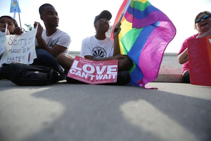 Local resident Carlos McKnight holds a rainbow flag in support of same-sex marriage