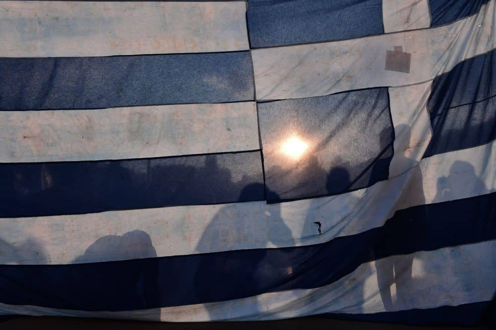 Protesters stand behind a huge Greek flag.