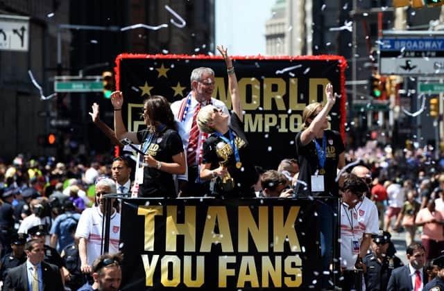 U.S. women's soccer team midfielder Megan Rapinoe (center) holds up the World Cup 2015 trophy as midfielder Carli Lloyd (left), New York City Mayor Bill de Blasio and head coach Jill Ellis (right) wave to the crowd during the ticker tape parade in New York on July 10, 2015.