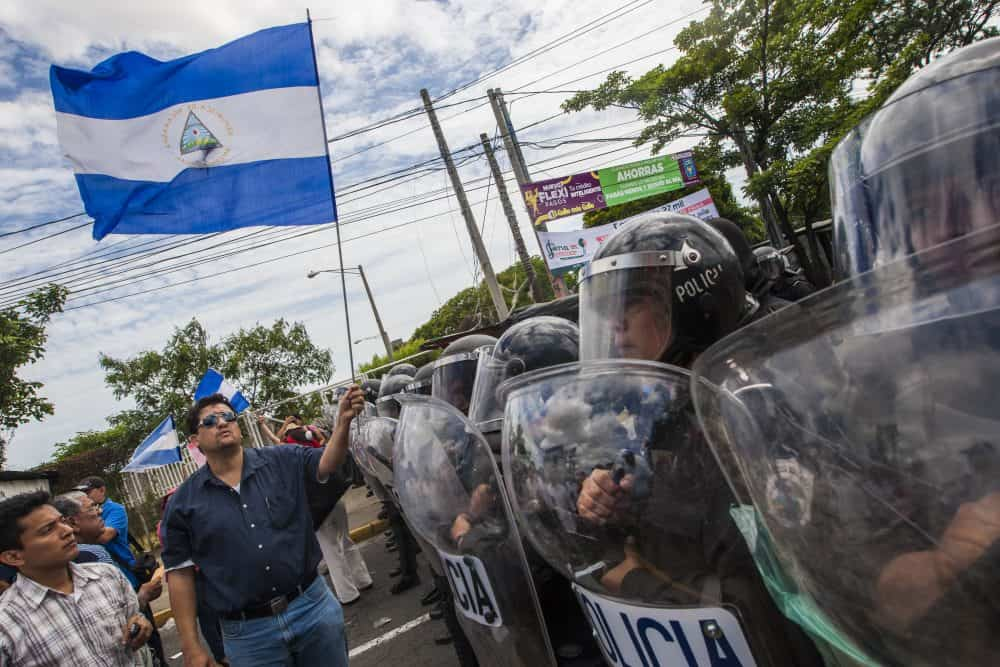 People flutter Nicaraguan national flags in front of a line of riot police as they protest against the electoral system in Managua, Nicaragua on July 15, 2015.