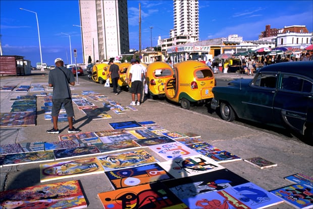 Paintings are spread out for sale at an outdoor flea market along Havana's oceanfront Malecón, 2015.