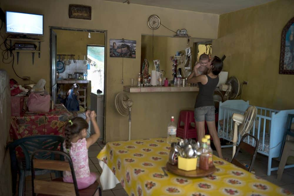 A girl holds her baby cousin at her family's restaurant on in Santiago De Los Caballeros, Mexico. This area is a base of operations for El Chapo's Sinaloa cartel and his support among the locals, combined with the area's rugged terrain, will make capturing him a challenge should he choose to return to the area, July 17, 2015.