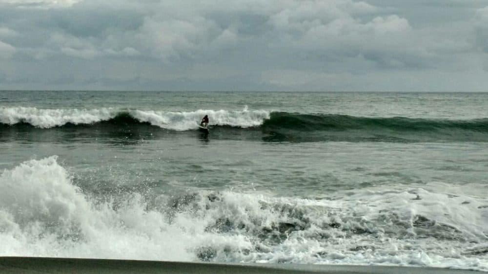 Surfer takes a wave at Playa Hermosa beach