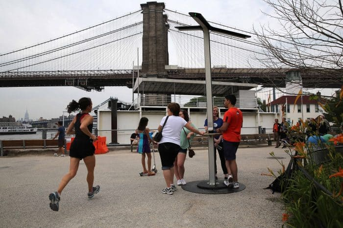 New Yorkers charge their cellphones at a free solar-powered charging station.
