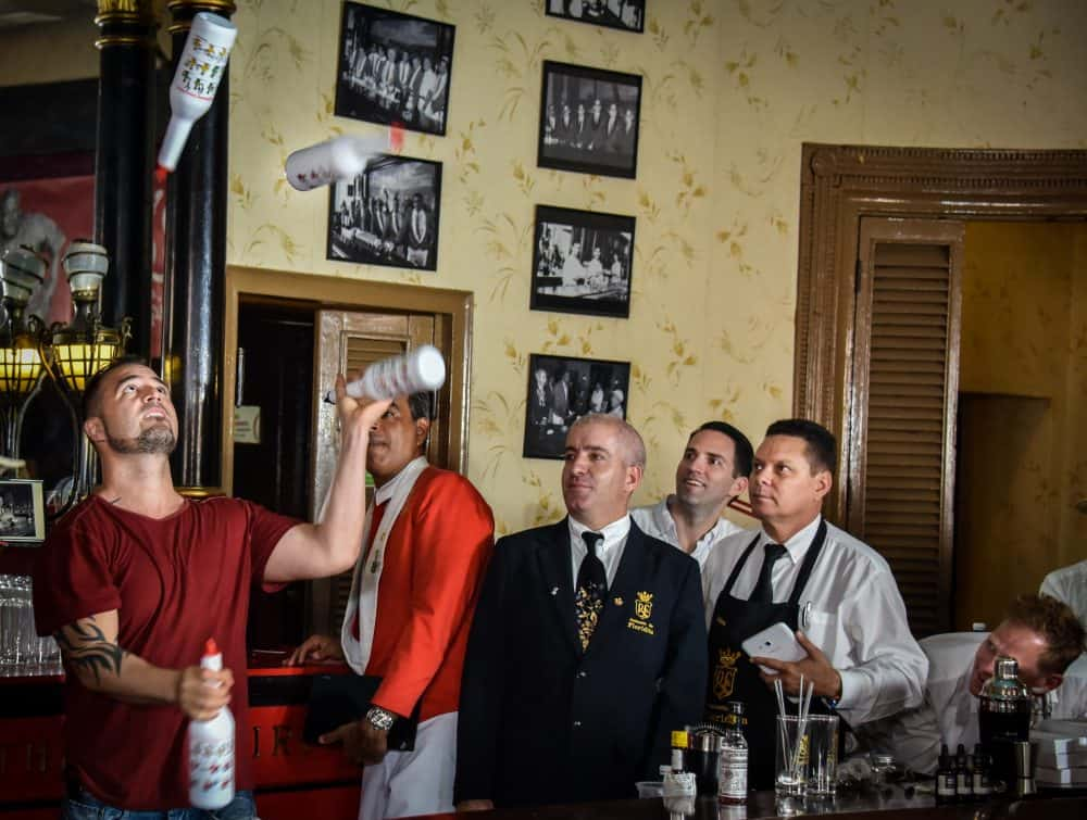 Argentine bartender Christian Delpech (left), who lives and works in Las Vegas, plays with bottles of rum at the Floridita bar in Havana, on July 24, 2015.
