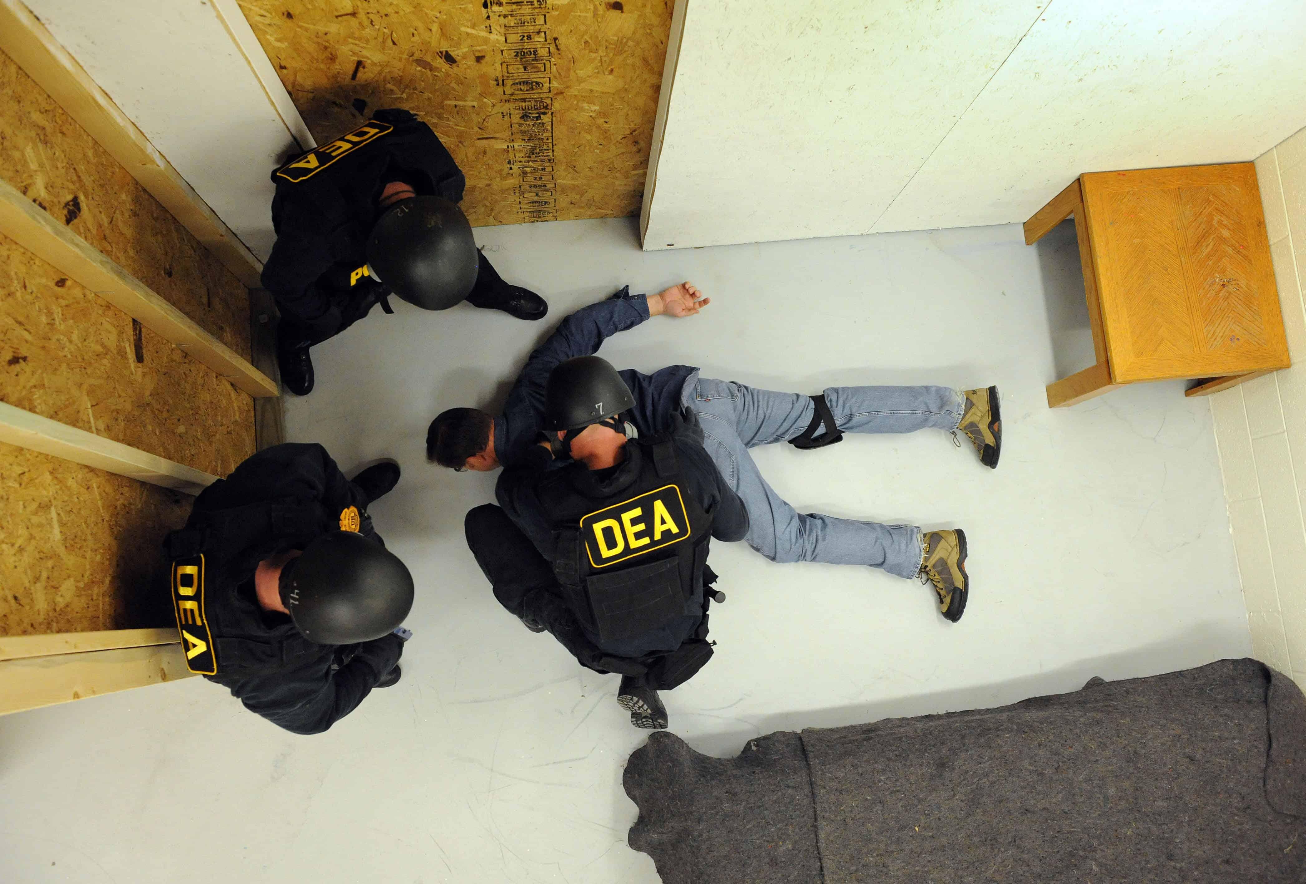 U.S. Drug Enforcement Administration (DEA) Agents simulate a raid.