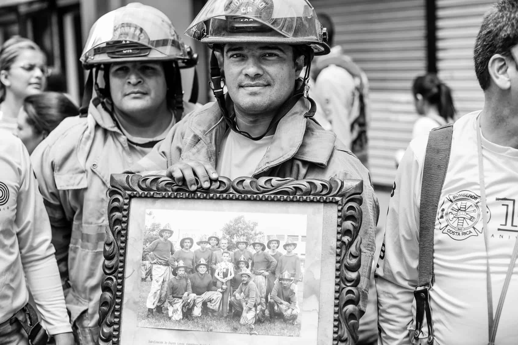 Firefighter Fran Guevara shows a picture of Costa Rican firefighters from 1952.