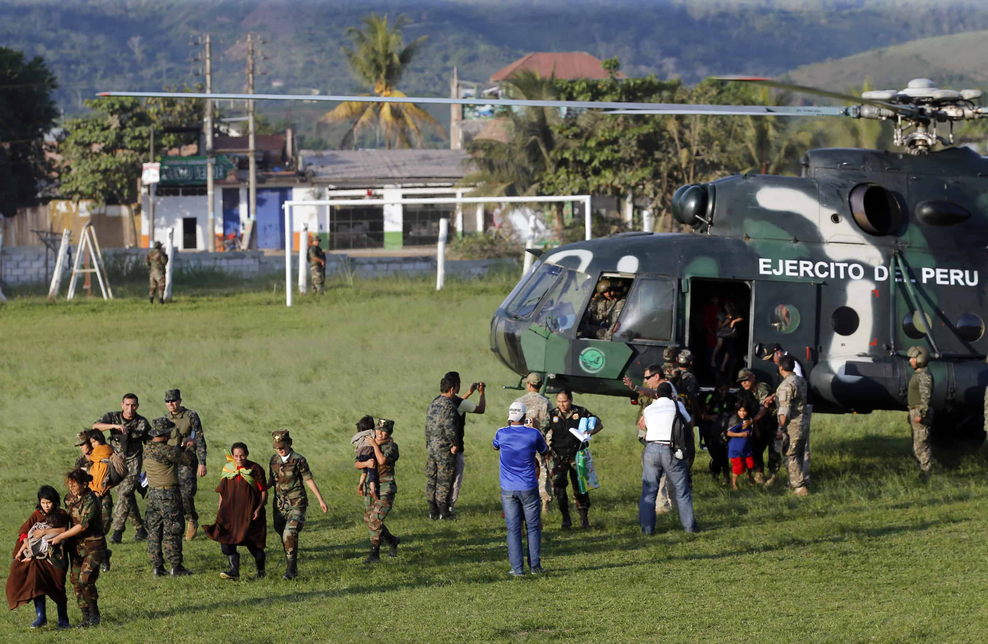 Peruvian Army soldiers usher adults and children to helicopters at the Air Force base in the jungle town of Mazamari.