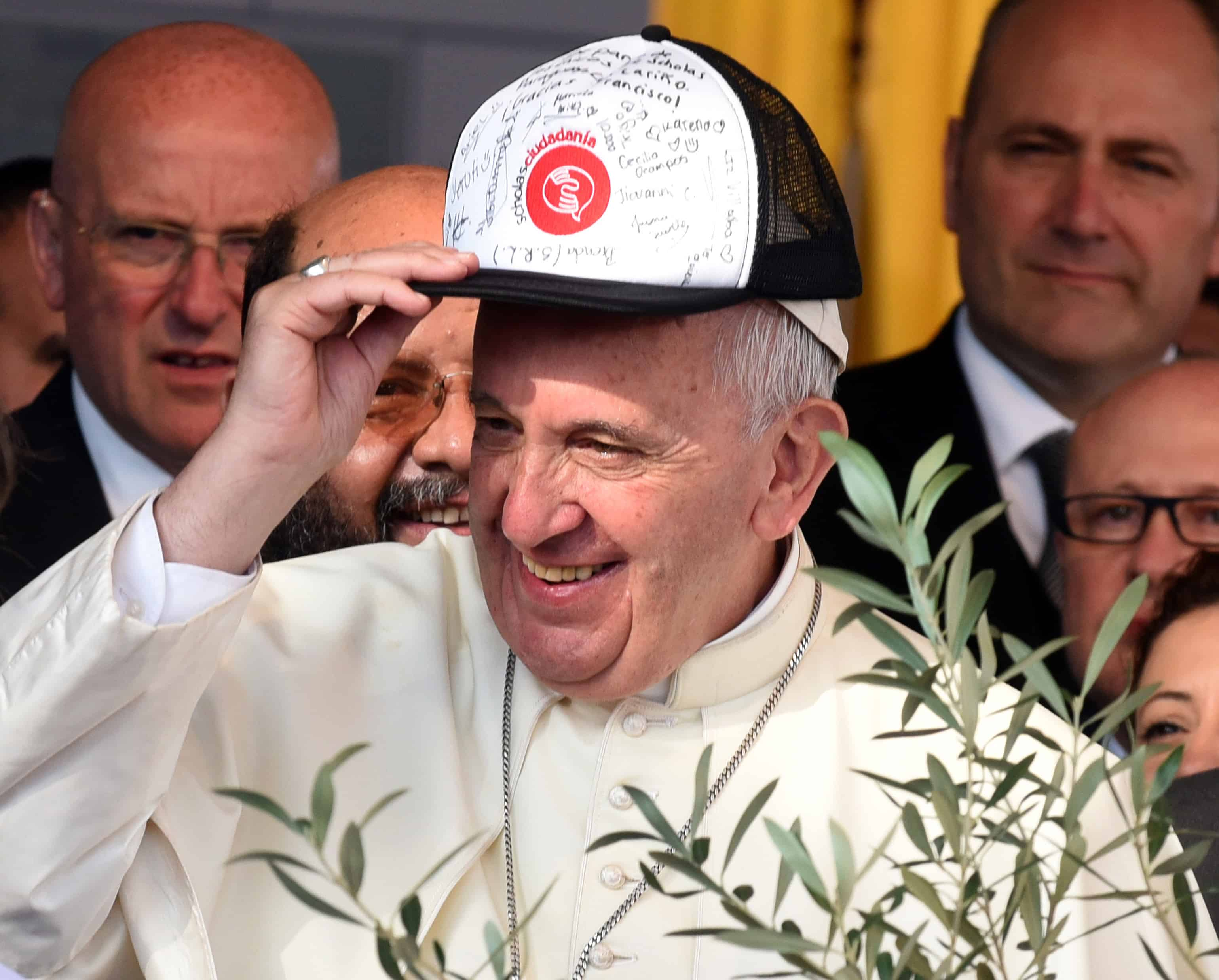 Pope Francis wears a cap signed by residents of Bañado Norte during his visit in Asunción.