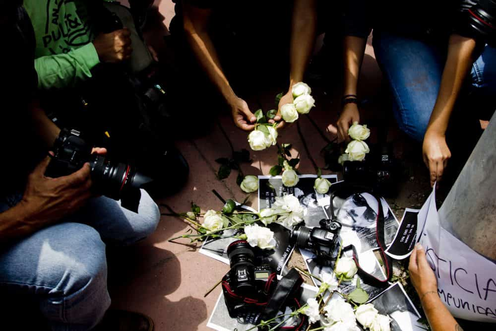 Mexican photojournalists place their cameras on the floor with white flowers .