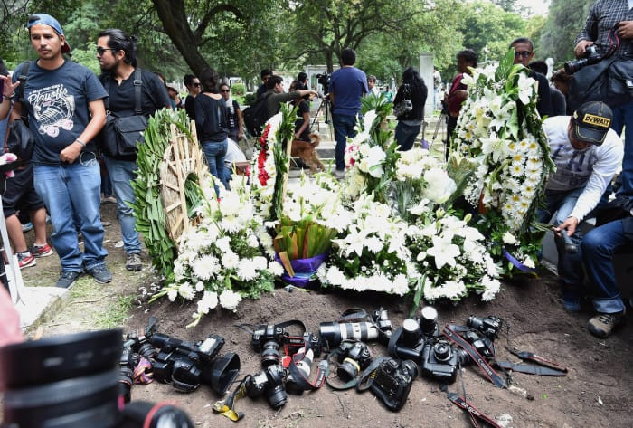 Colleagues of murdered Mexican photographer Rubén Espinosa place their cameras beside his grave .