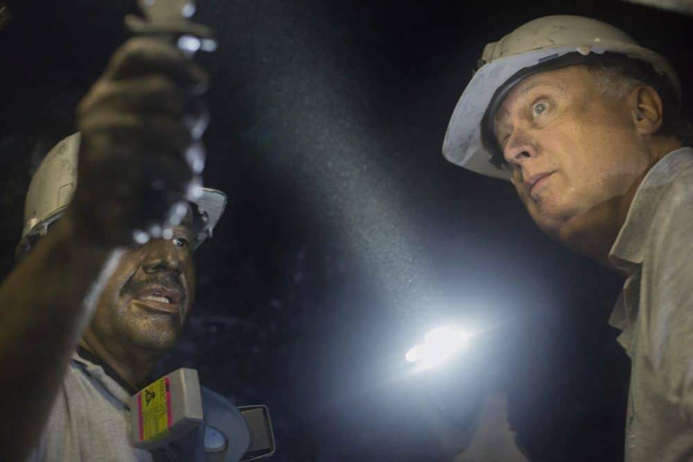 Miner Daniel Guerrero, left, shows a rock to Charles Burgess, director of Minería Texas Colombia in Muzo, Colombia on July 24, 2015.