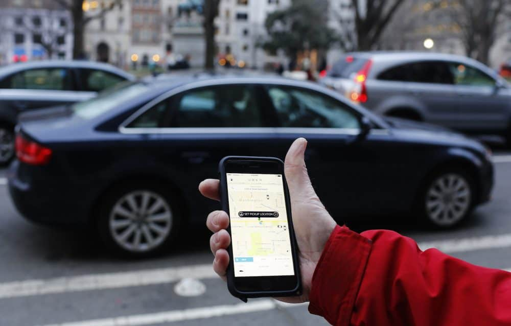 This March 25, 2015 file photo shows an UBER application viewed as cars drive by in Washington, DC.
