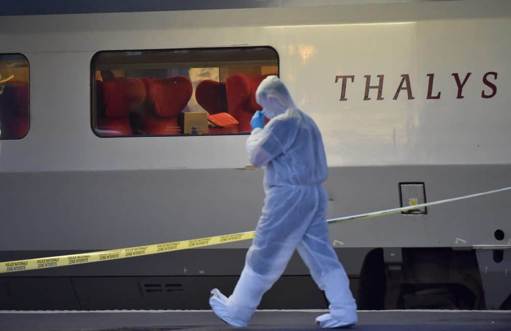Police officers walk on a platform next to a Thalys train.
