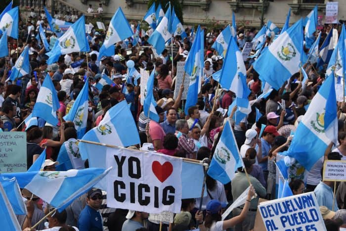 """Protesters wave Guatemalan flags and a sign reading """"I love CICIG."""""""