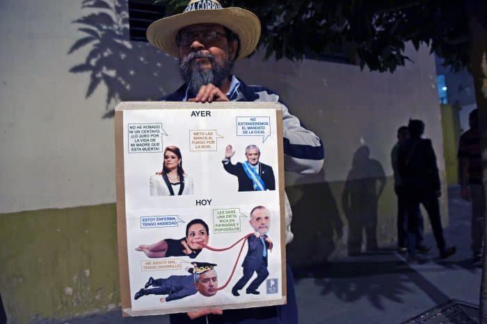 A man holds a sign with pictures of Guatemalan President Otto Pérez Molina, ex-Vice President Roxana Baldetti and the chief of the International Commission Against Impunity in Guatemala, Iván Velásquez.