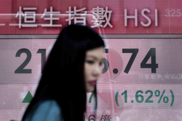 A woman walks past an electronic board displaying financial information in Hong Kong.