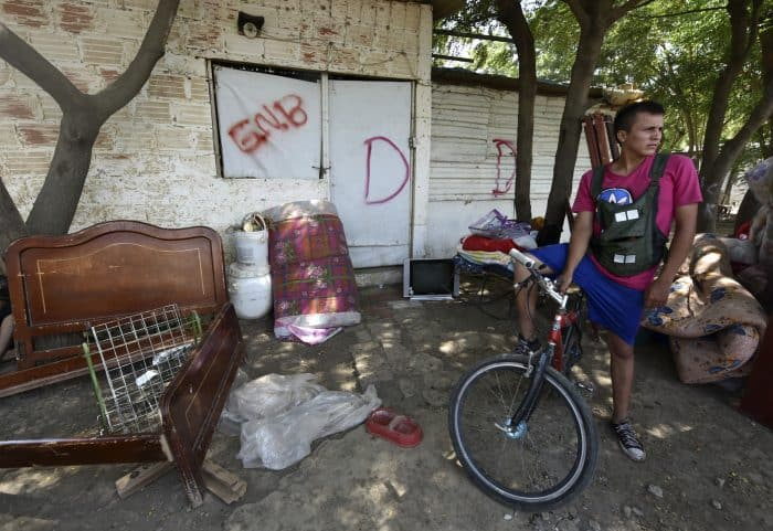 "A Colombian who was deported from Venezuela waits in front of his now former house, marked with a ""D"" for demolition, in San Antonio de Táchira, Venezuela, where he returned for his belongings to carry them across the bordering Táchira River, on Aug. 25, 2015."