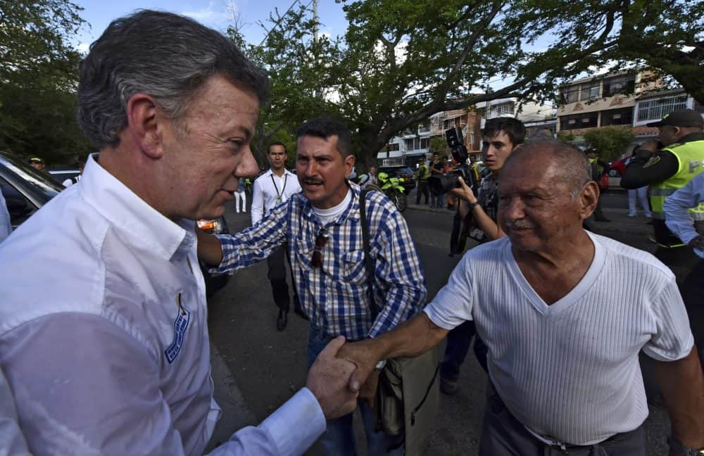 Colombian President Juan Manuel Santos, left, shakes hands with a man during a visit to a shelter in Cucuta, Colombia.