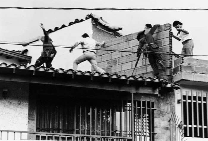 Colombian police and military forces storm the rooftop where drug lord Pablo Escobar was shot dead.