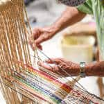Don Tina mounts the thread in his loom.