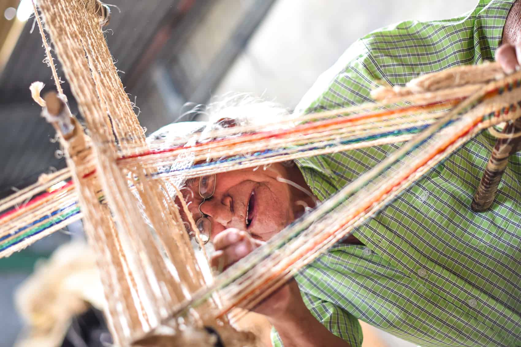 Juan Olivado Camacho, known as Don Tina, 74, explains how he uses a loom and cabuya thread to make products.