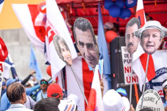 Heads of lawmakers are carried as protest signs at the public employee demonstration in Avenida Segunda, San José, August 20, 2015.