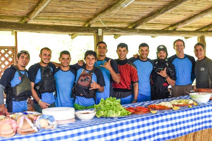 Guides, kayakers and friends: Lunch is served. Daniel Bustos Araya, making the hand sign at center, leads rafting, canopy and canyoning tours and does mixed martial arts in his spare time.