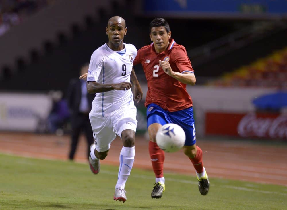 Costa Rica's Johnny Acosta (R) races for the ball with Diego Rolan (L) of Uruguay during La Sele's 1-0 win at the National Stadium in San Jose, Costa Rica, on Sept. 8, 2015.
