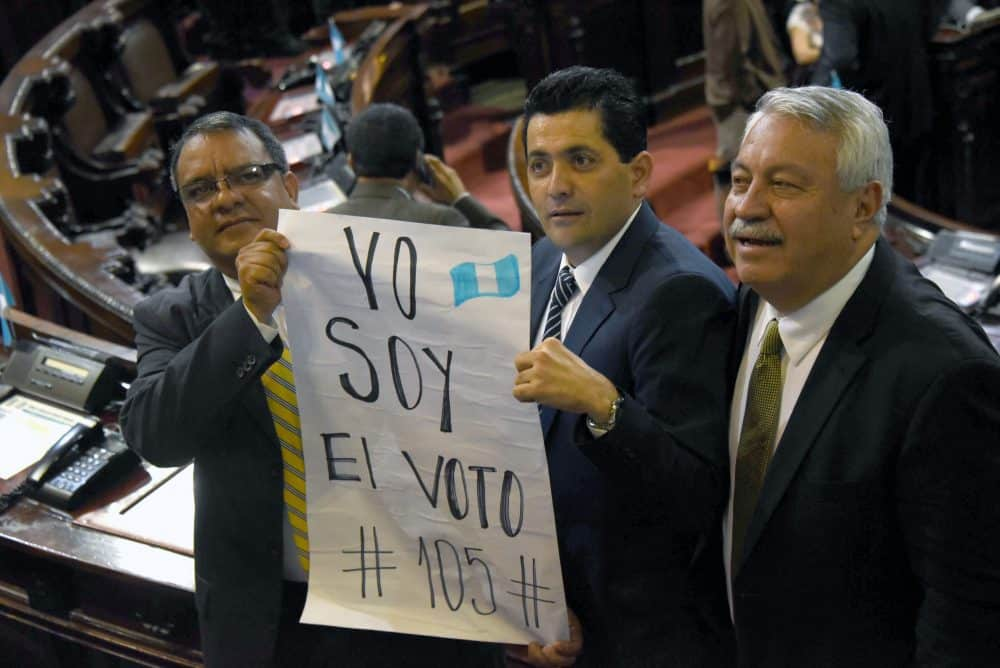 """Guatemalan lawmakers Celvin García, left, Óscar Chinchilla, center, and Carlos Fión hold a sign that reads: """"I Am Vote #105."""""""