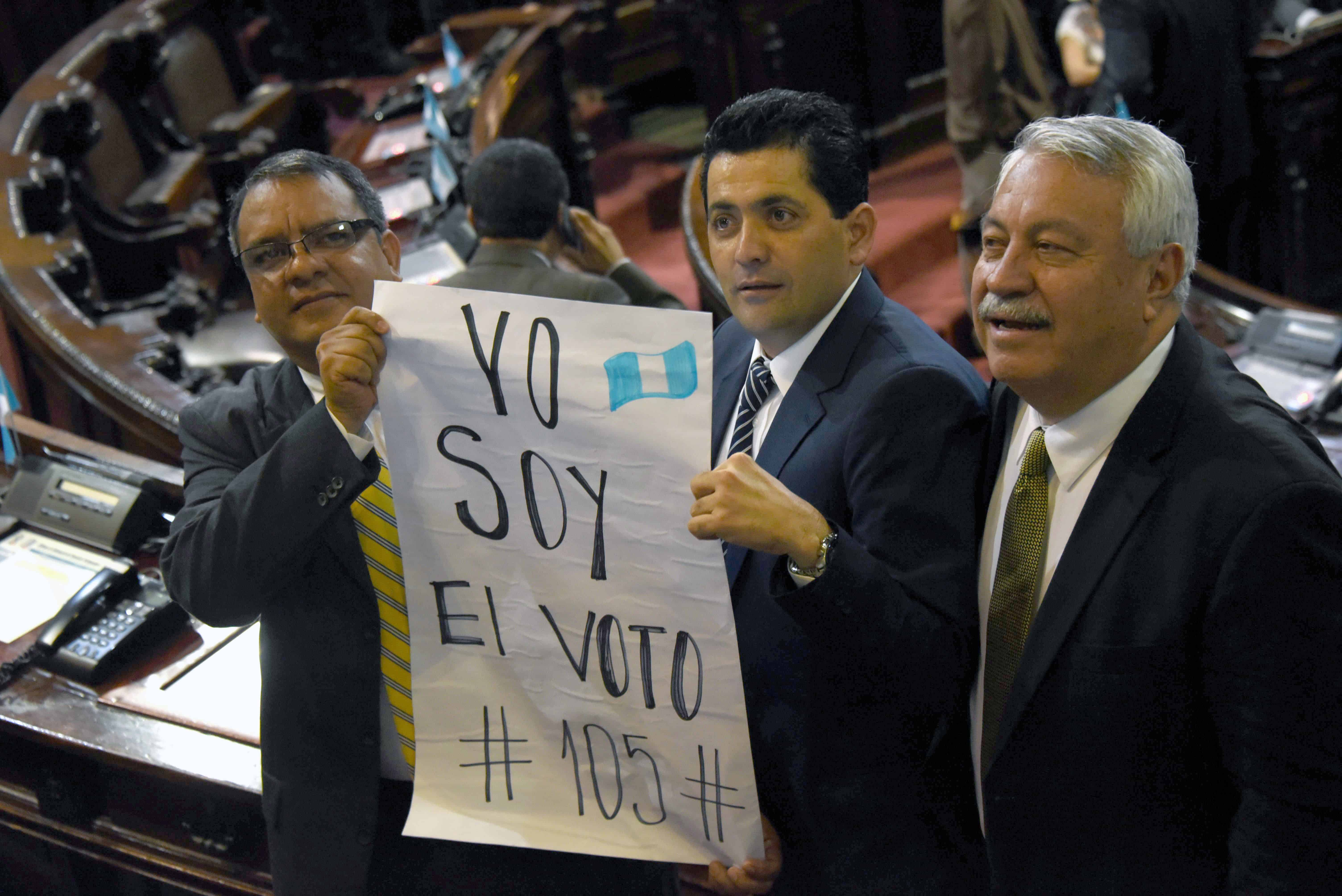 "Guatemalan lawmakers Celvin García, left, Óscar Chinchilla, center, and Carlos Fión hold a sign that reads: ""I Am Vote #105."""