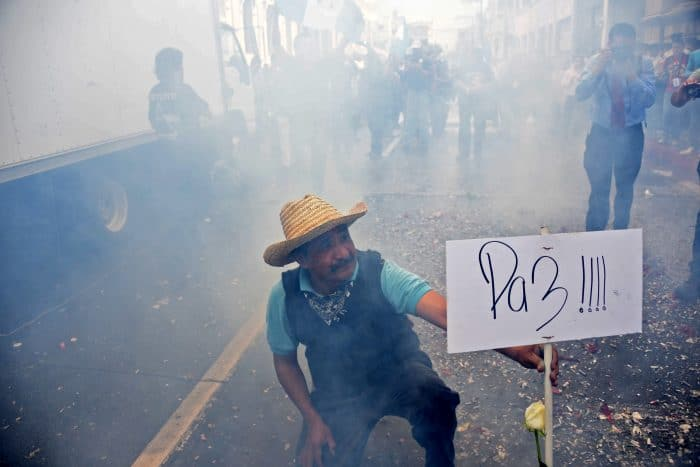 """A man holds a sign declaring """"Peace"""" after the Guatemalan Congress voted unanimously to strip embattled President Otto Pérez Molina's immunity."""