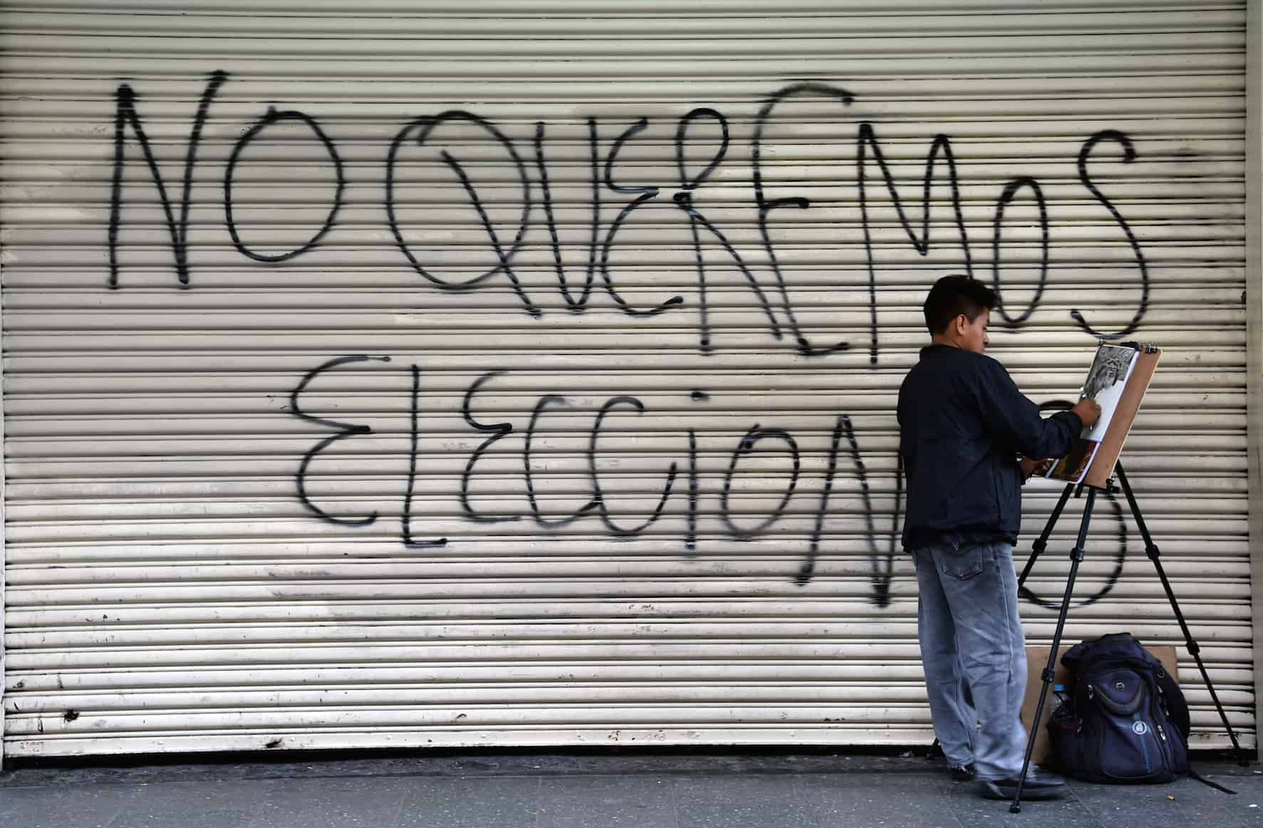 "A man paints next to a graffiti reading ""We don't want elections"" on the eve of general elections in Guatemala City on Sept. 5, 2015. Guatemalans disgusted with rampant corruption that felled their president are set to vote Sunday in elections many see as meaningless without a vast political system cleanup."