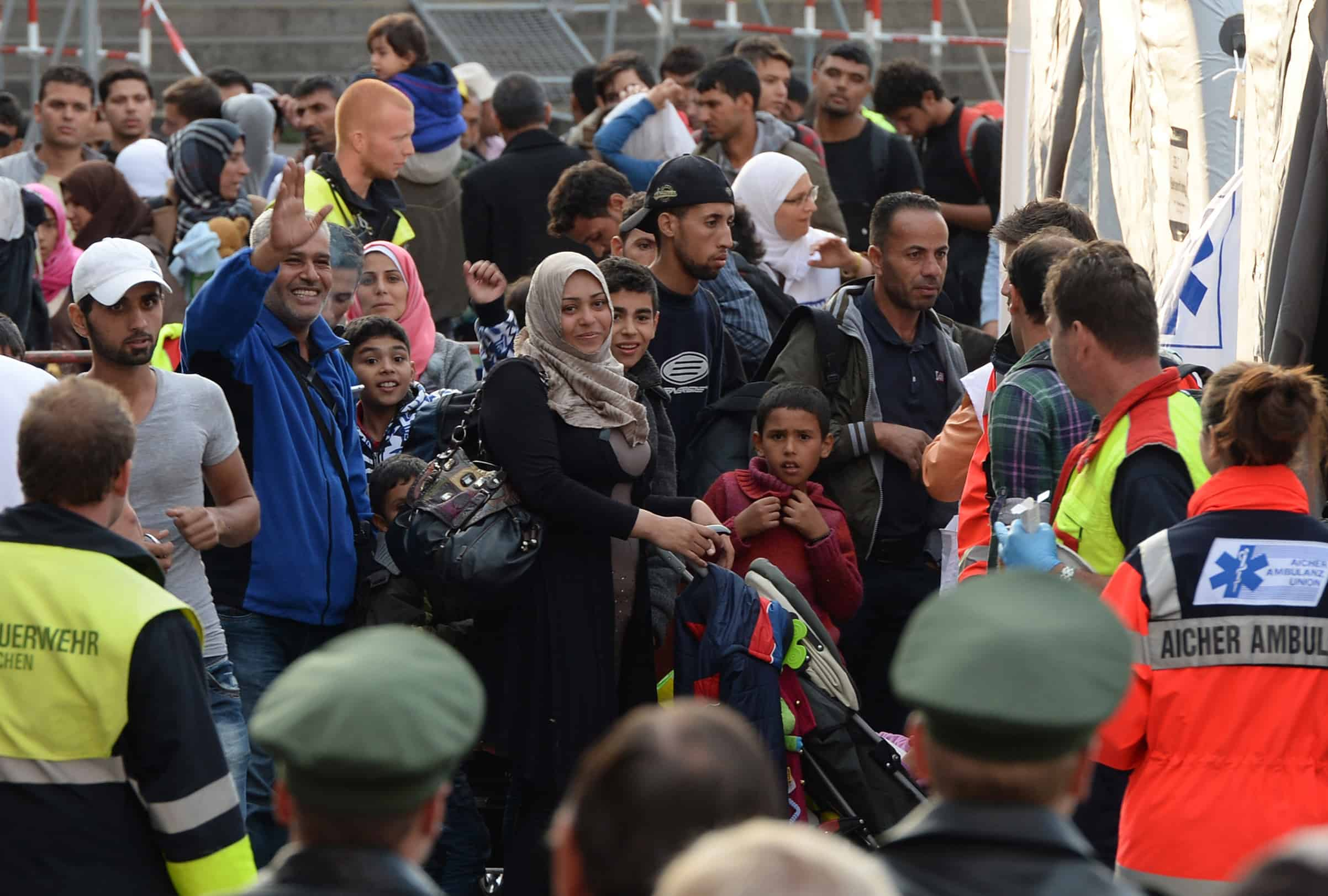Incoming refugees wait for a short first medical check after their arrival in front of the main train station in Munich, southern Germany, Sept. 5, 2015.