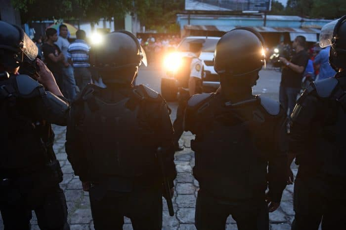 National police officers stand guard outside a polling station in San José del Golfo, 28 km northeast of Guatemala City, on Sept. 6, 2015. Guatemalans streamed to the polls Sunday in general elections held amid public disenchantment with government just days after the country's president was jailed on corruption charges.