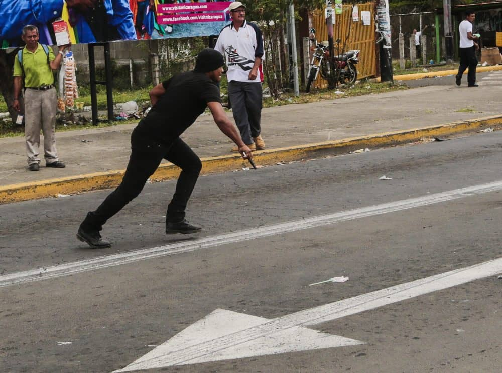 A Sandinista supporter runs with a pistol when chasing opposition members during a protest against the electoral system in Nicaragua, in Managua, on Sept. 2, 2015.