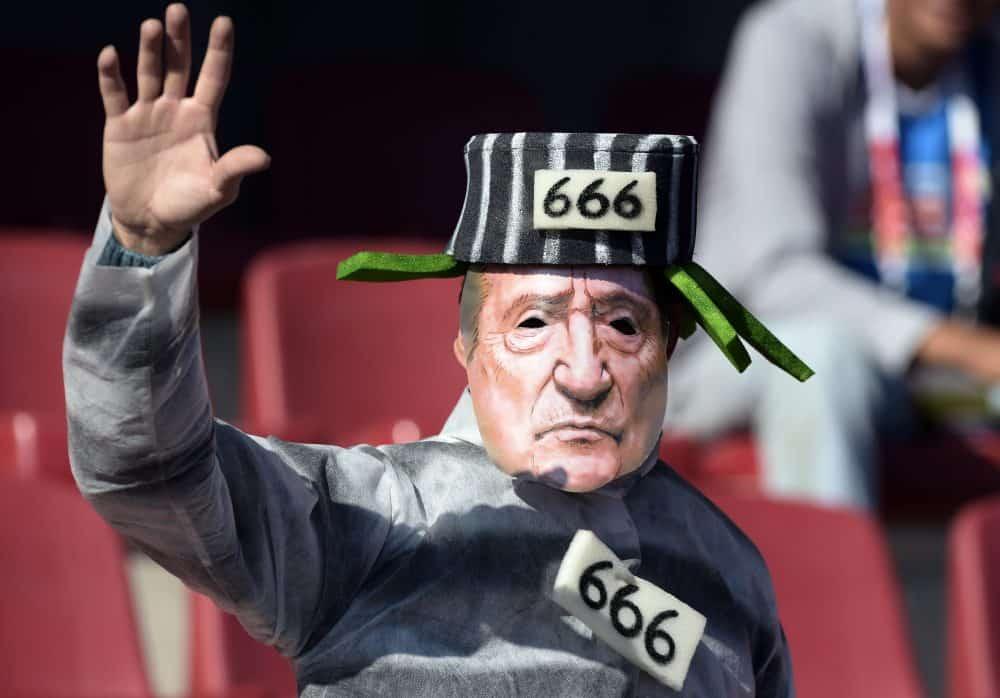Following FIFA corruption probe, a fan sports a Eugenio Figueredo mask.