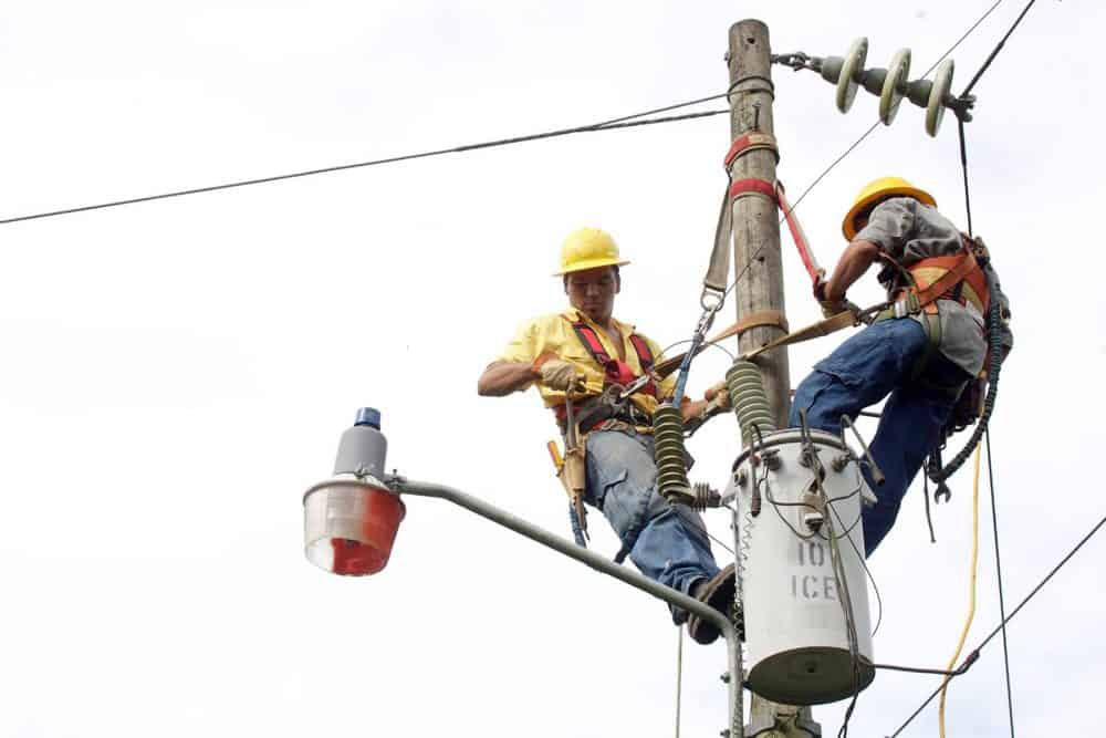 electricity workers on power line post