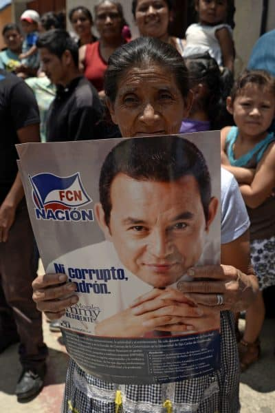 woman with poster of Jimmy Morales