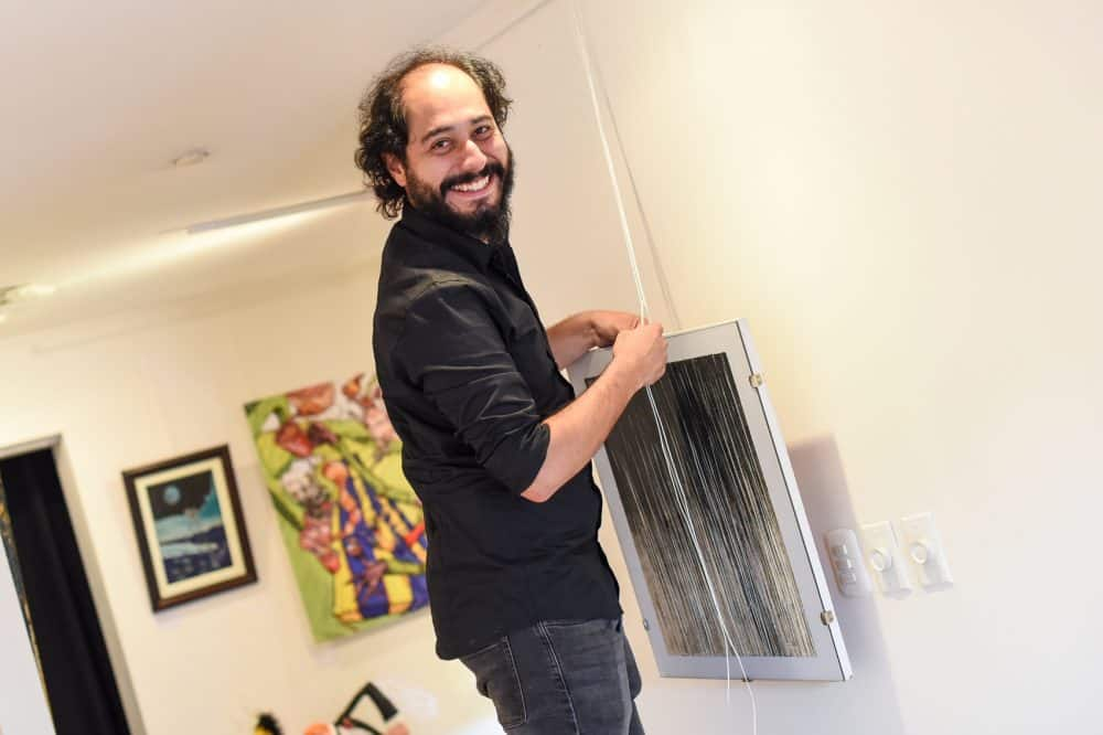 "Artist Brian Breness hangs a piece of art from Costa Rican artist Rafael ""Felo"" García in his gallery in Barrio Escalante."